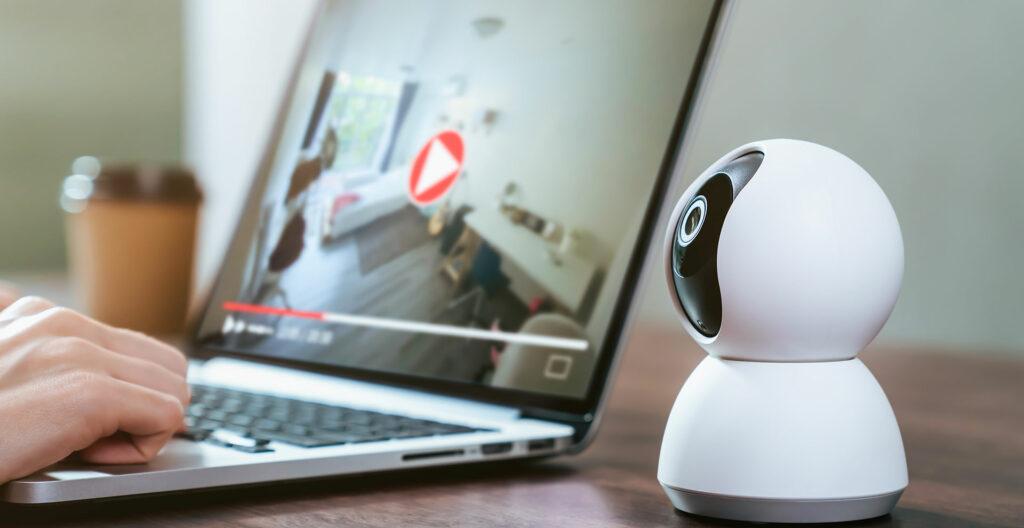une camera est posée sur un bureau et une personne regarde les images sur un ordinateur pour représenter le kit alarme de comfort life