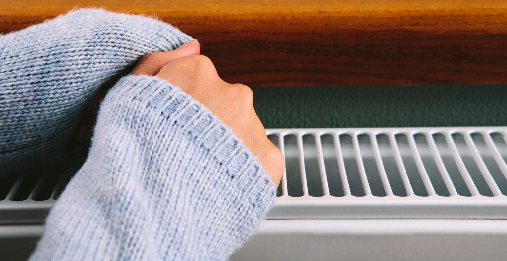 deux mains de femme se réchauffe près d'un chauffage pour représenter le kit chauffage de comfort life